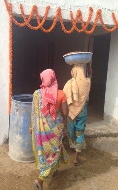 Two women who live near the school built by Cummings' church carry a tray through a doorway decorated for Diwali. Photo courtesy of Tiffany Cummings.